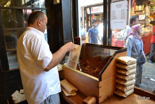 صاحب مغازه در حال آماده سازی بسته های قهوه. قهوه ترک معمولا به شکل آسیاشده به فروش می رسد.