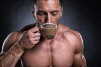 Studio shot of male fitness athlete while drinking coffee.